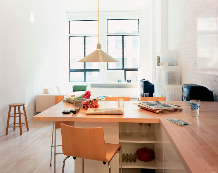 "The combination dining table/countertop, says Woo, ""is both a demarcation and connection between the kitchen and main living space."" Originally, the architect considered a concrete surface, but balked at the delivery time and expense. ""I kind of like it a"