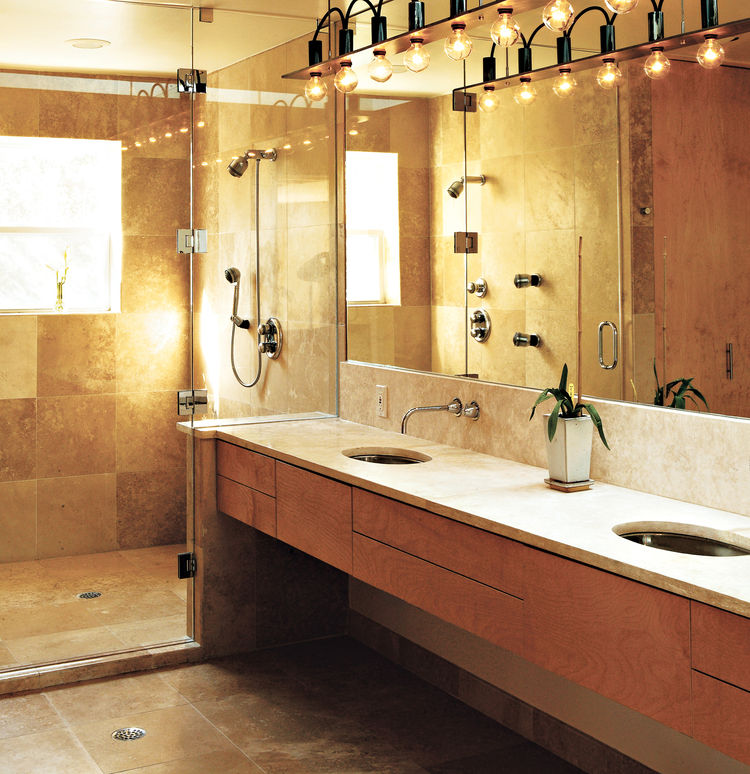 "The master bath is a simple rectangle. ""Like the kitchen, I designed it so that no stuff was laying around,"" Erik said. The surfaces are natural and subdued; a simple palette of tones, colors, and materials unifies the space. Travertine marble was used on"