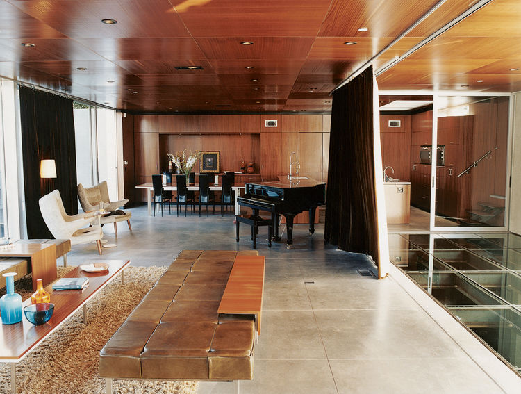 In the humidor-like living room, modern classics like the off-white armchairs by Hans Wegner complement pieces of Segal's own design, such as the coffee table and long leather seating.