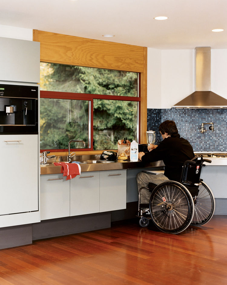 Meal prep is simplified for Siple. All the cabinets are easy to open, there's space under the cooktop for his wheelchair, and a faucet over the range removes the need to haul pots to the sink for filling.