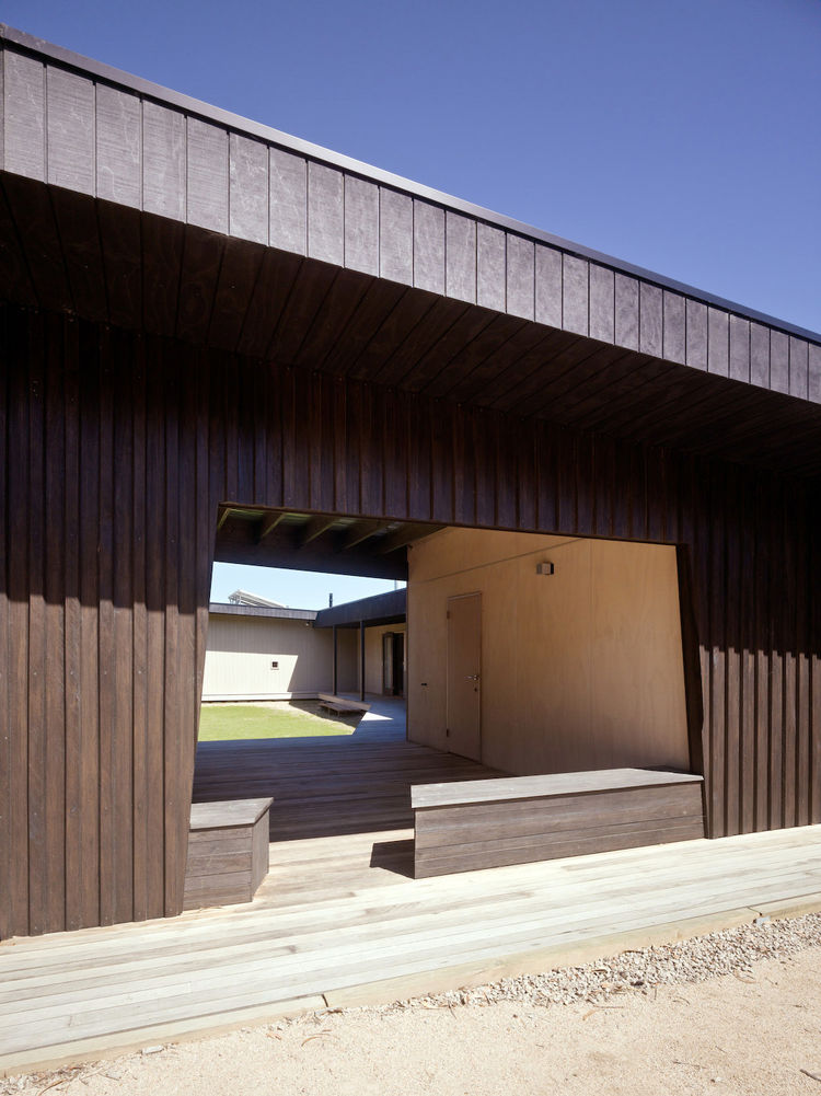 "Rowan told me that he wanted ""the radial-sawn timber cladding to act like a drape. Then the house would have these shapely openings, like keyholes."" This view from the front shows how Rowan used the deep shadows not only as cooling devices, but as an actu"
