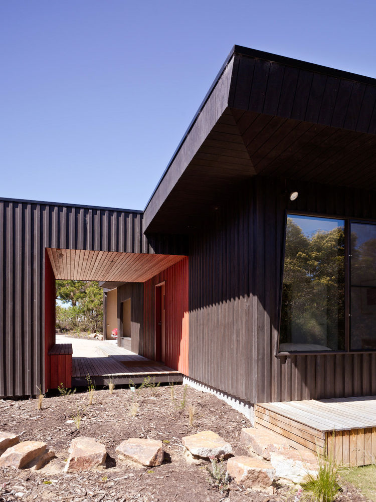 The entryway of the house, as seen from the garden, was devised as a kind of red carpet into the home. It looks great set against the black exterior. Just behind the entry is the black-clad water filtration system.