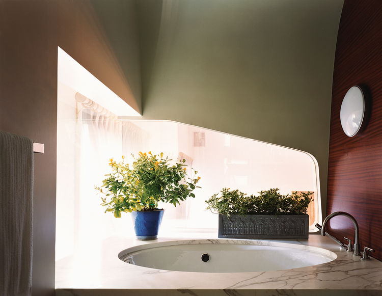 The window beside the tub in the master bathroom peers over the living space below and echoes the shiplike quality of the pod, which also contains the master bedroom. Lights reminiscent of portholes and mahogany walls deepen the feeling of being on an oce