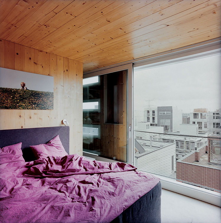 In the master bedroom, a large window looks out onto the surrounding rooftops.