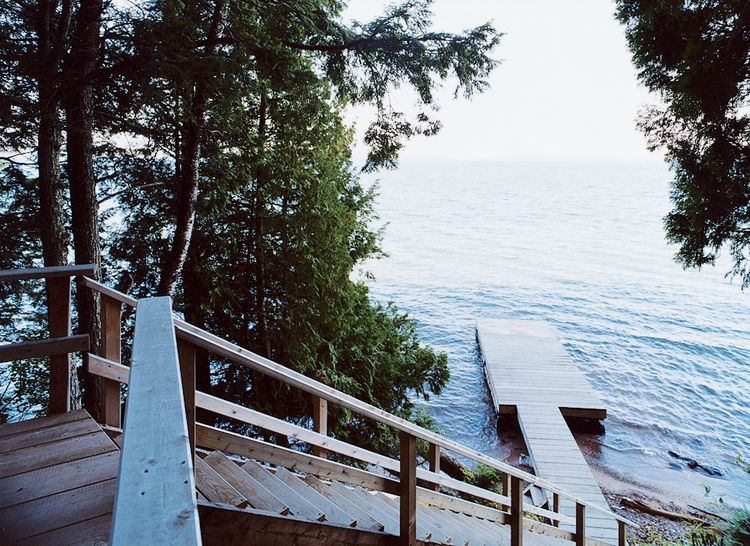 A wooden stair leads from the house down to a dramatic view of Lake Superior.