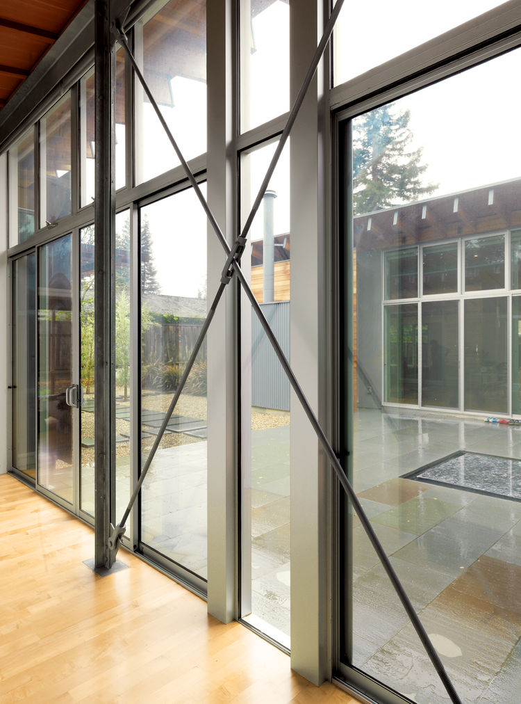 Tension rods provide bracing for the glass walls, and exposed bolts reveal how everything is put together.