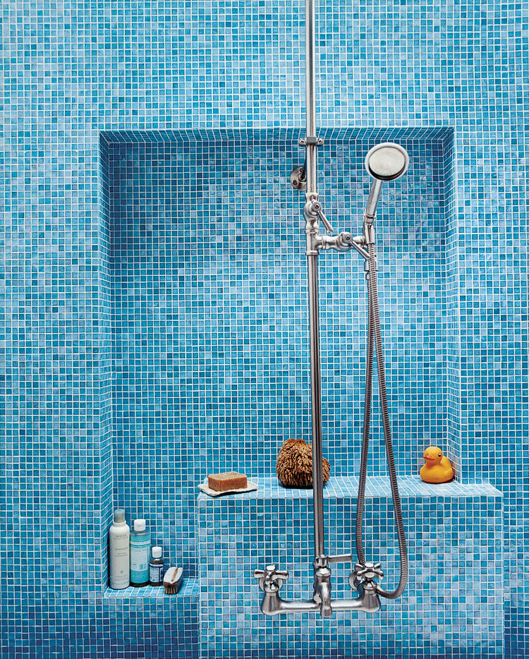The bathroom glows with various shades of Turkish-style glass tiles (in Iris) from Galleria Tile in San Francisco; the custom nickel-plated hardware is from Chicago Faucets.