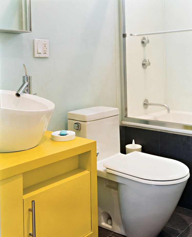 To save money and time, the architects used similar designs for the bathrooms  in both their and Andy's apartment: Philippe Starck toilets, fixtures from New York's AF Supply, and custom cabinets painted with watertight auto-body paint.