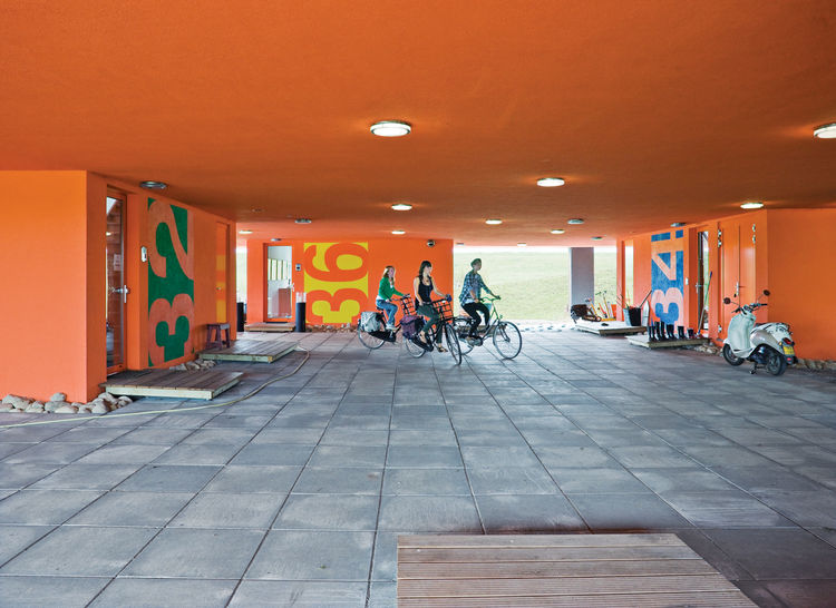 "The communal entrance beneath the building is known as the ""public square""; sisters Tessa and Anne Bouwmeester and a friend set off on their bikes."
