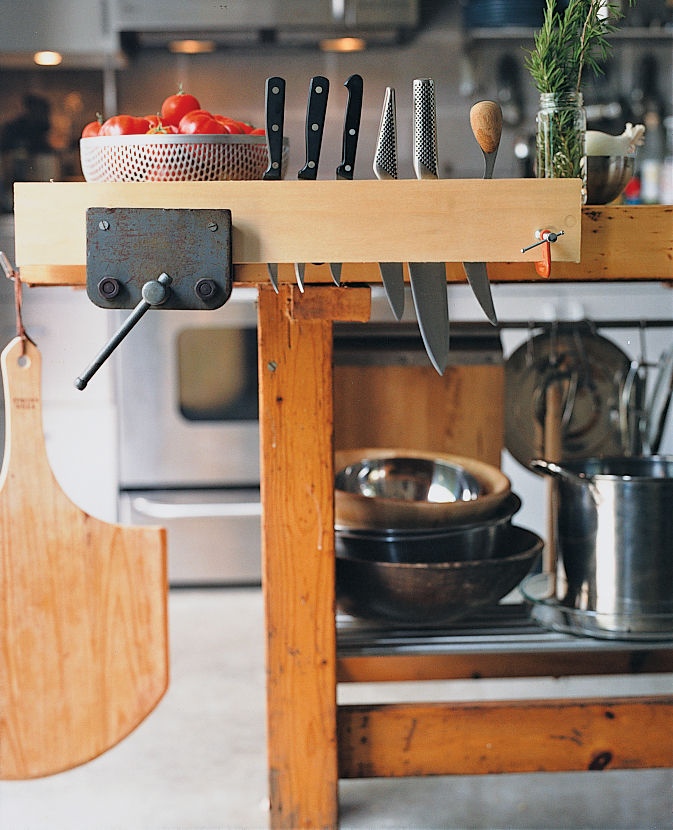 "Summit created a functional kitchen island out of Walz's childhood workbench, fitting  it with various IKEA parts. The vice makes an ideal wine grabber, and pieces of black iron pipe hold candles. ""Now it's very Martha Stewart,"" jokes Summit."