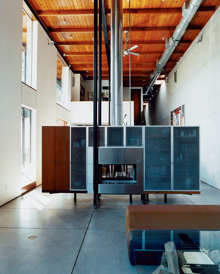 David Baker and cabinetmaker Thomas Jameson designed the freestanding fireplace / media console, which effectively divides the more formal living room from the dining and gathering space while concealing cords and other clutter.