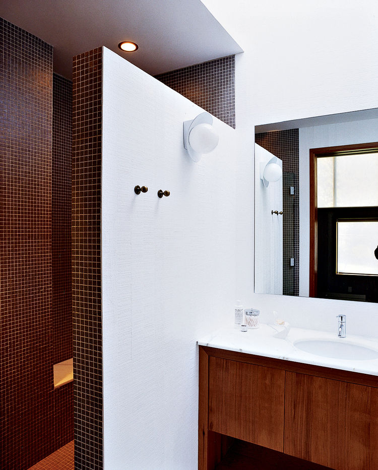A double-size shower, clad floor-to-ceiling in tiny earth-toned tiles, was built after relocating the water heater and claiming its space. A chic yet discreet toilet is wall-hung and the tank concealed, greatly ameliorating the somewhat claustrophobic fee