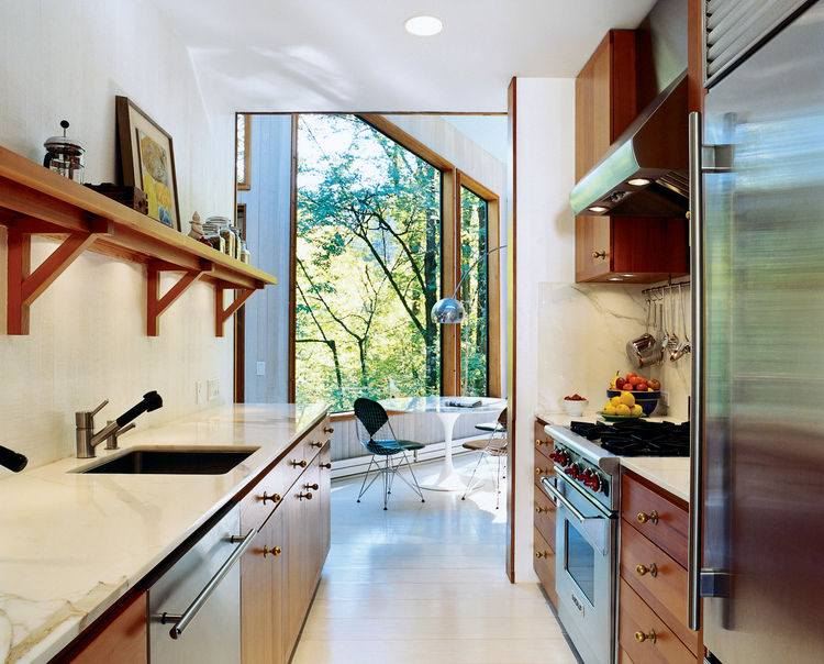 To brighten the kitchen, which was once the darkest room, Watson and Tschopp decided on a glossy white finish, painted directly on the same rough-cut cedar paneling used throughout the house. This maintains the consistency of materials and texture, while