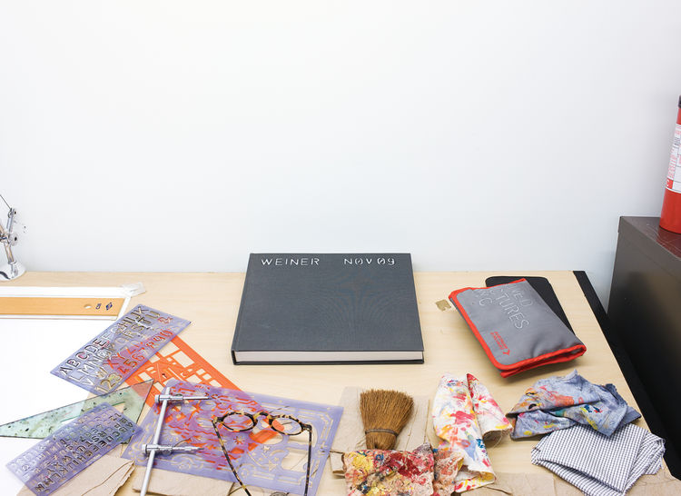 A collection of objects from Lawrence's desk include stencils, paint rags, glasses, and a notebook.