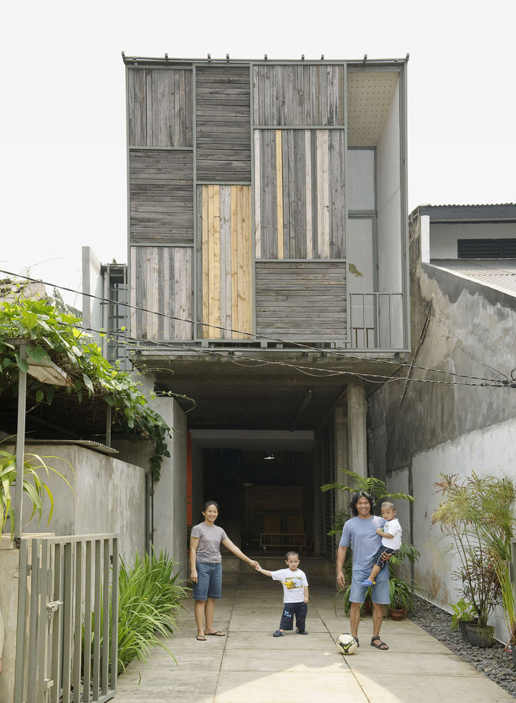 The family poses in the driveway out front of the house. The sliding panels on the facade allow a peek into the balcony just inside.