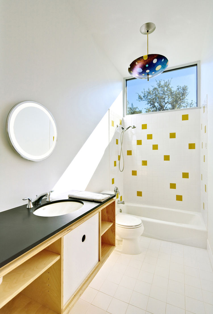 "Light floods the second-floor bath, which is housed within a birch-ply ""box"" also containing storage. The water is heated by a tankless, on-demand unit from Rinnai. The architects continued the tile motif for the bath downstairs; the honey-colored tiles a"