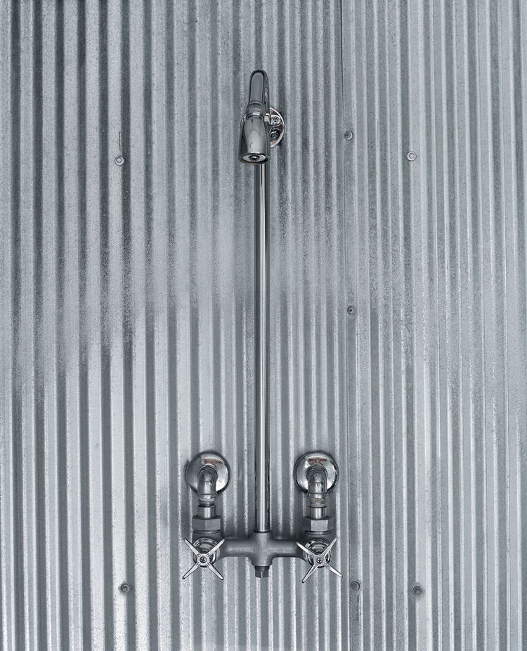 A simple shower design using corrugated steel references farmhouses of old.