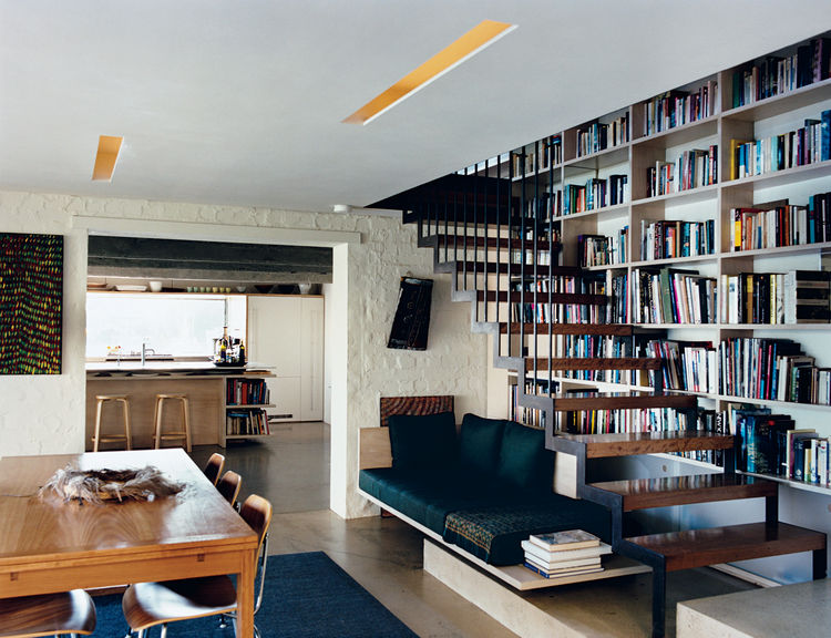 Inside, a suspended staircase rises up past the couple's bookcase over a well-lit seating nook.  Aalto stools by Artek join Eames molded plywood dining chairs by Herman Miller to give an especially modern touch to the kitchen.