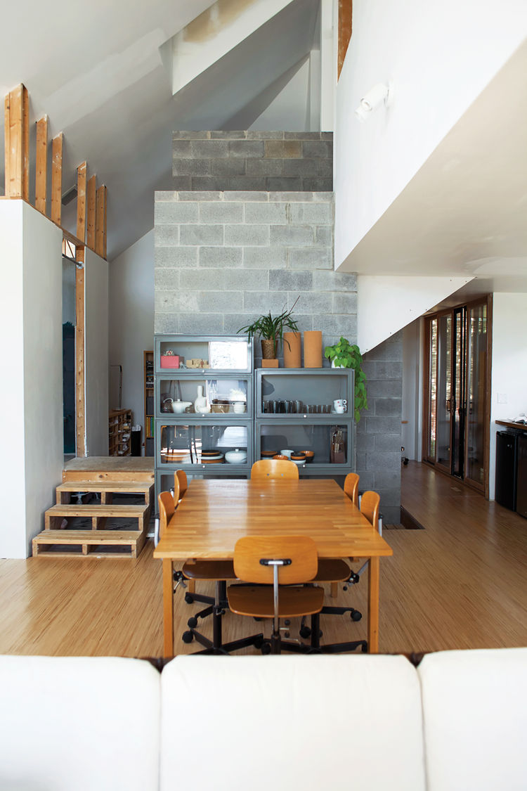 Dining area with small staircase concrete fireplace