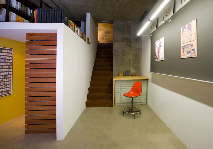 Nestled between an existing concrete wall at right and the new reading loft at left is the entrance staircase, which Colkitt sheathed in rusted steel panels. He used Homasote, invented in 1909 and made from recycled post-consumer paper, for the work board