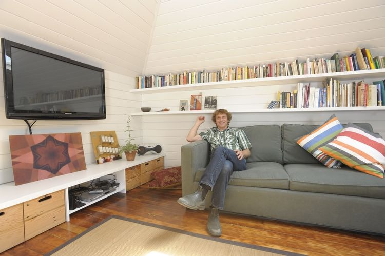 Here's Defauw in his living room. He and the rest of the renovation team patched and refinished the original fir floors. The walls are inexpensive pine siding sprayed with white oil paint. The shelves above are 1/4-inch plywood perched on makeshift rods m