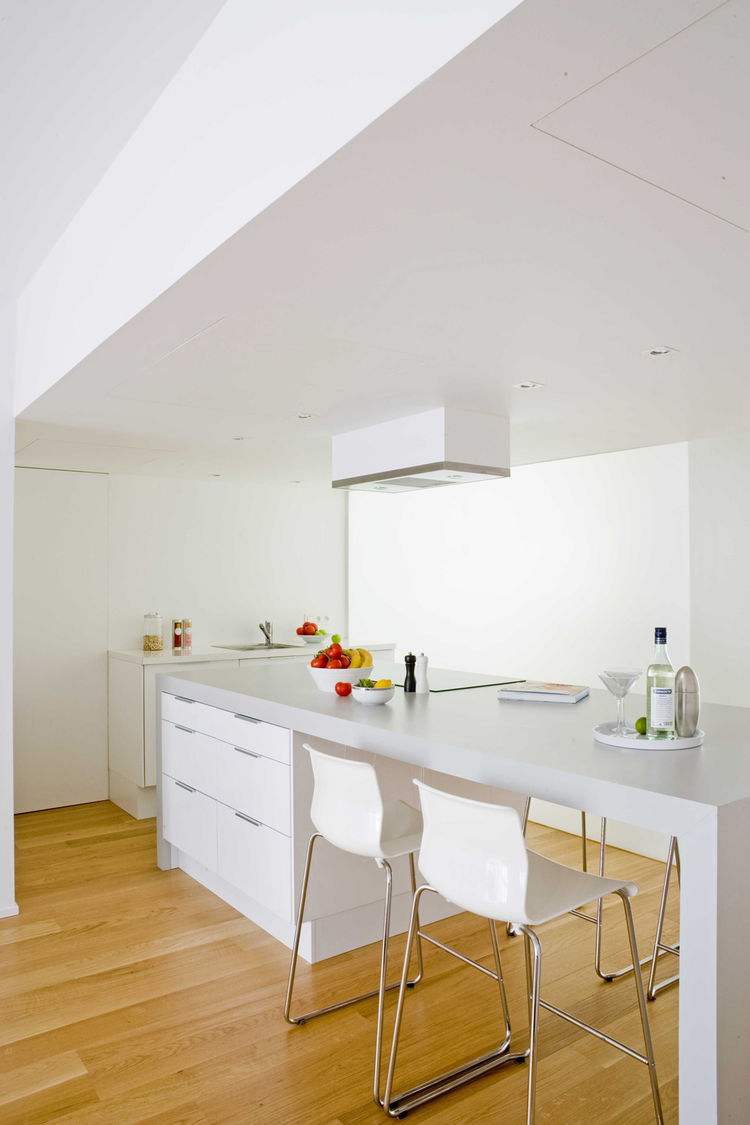 "A drop ceiling defines kitchen and dining area and also provides storage. ""It's the basement we never had, hidden right in plain sight,"" says Rios. ""The other thing that's worked well about the dropped ceiling is that it creates a sense of intimacy when w"