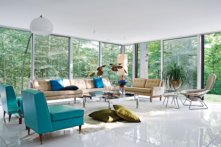 The living room, with vintage furnishings by Harry Bertoia, Paul McCobb, and others, overlooks the heavily wooded site, which adjoins a protected watershed. Goddard and Mandolene replaced the original tile floor with a glossy coat of resin and restored th