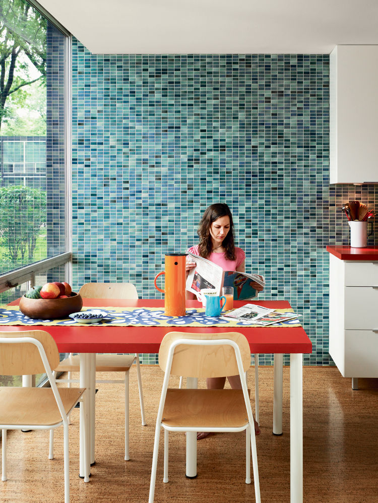 Because the original kitchen had been removed, Alexandra made the decision to widen the gallery-style room by ten inches. Floor-to-ceiling glass makes for ample natural light in the eating area, while the Vitra wall tiles provide a contemporary touch.
