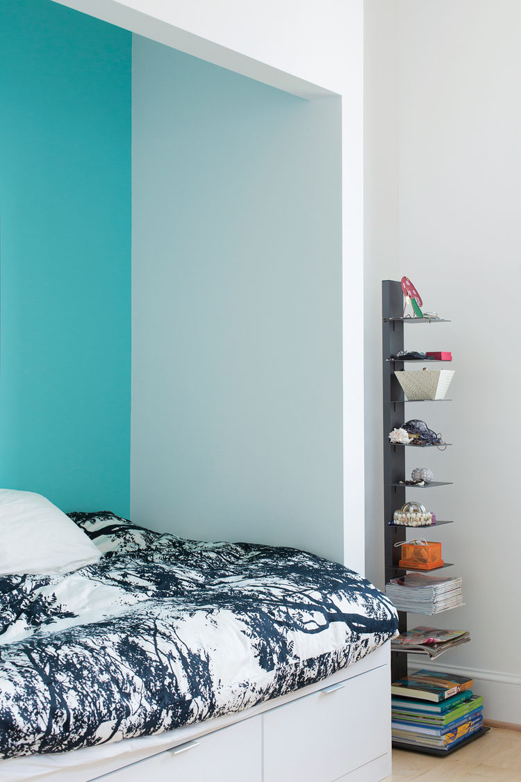 Modern bedroom design with blue walls, black and white duvet, and metal bookshelf