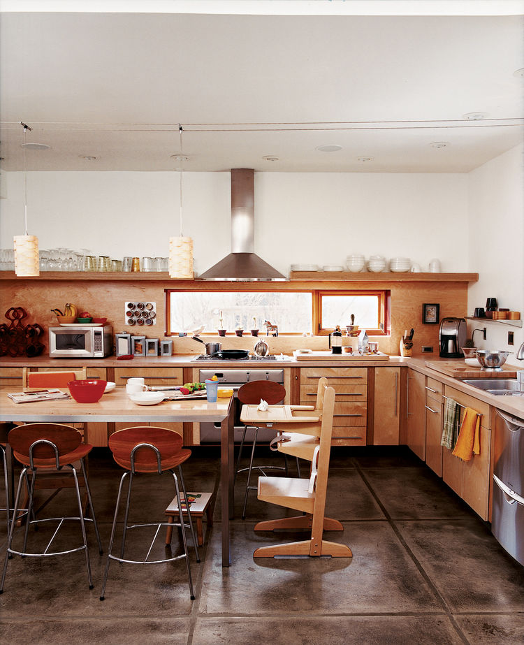 In the kitchen, a window over the stovetop lets daylight in, framing the front yard while keeping the neighboring house out of the picture.