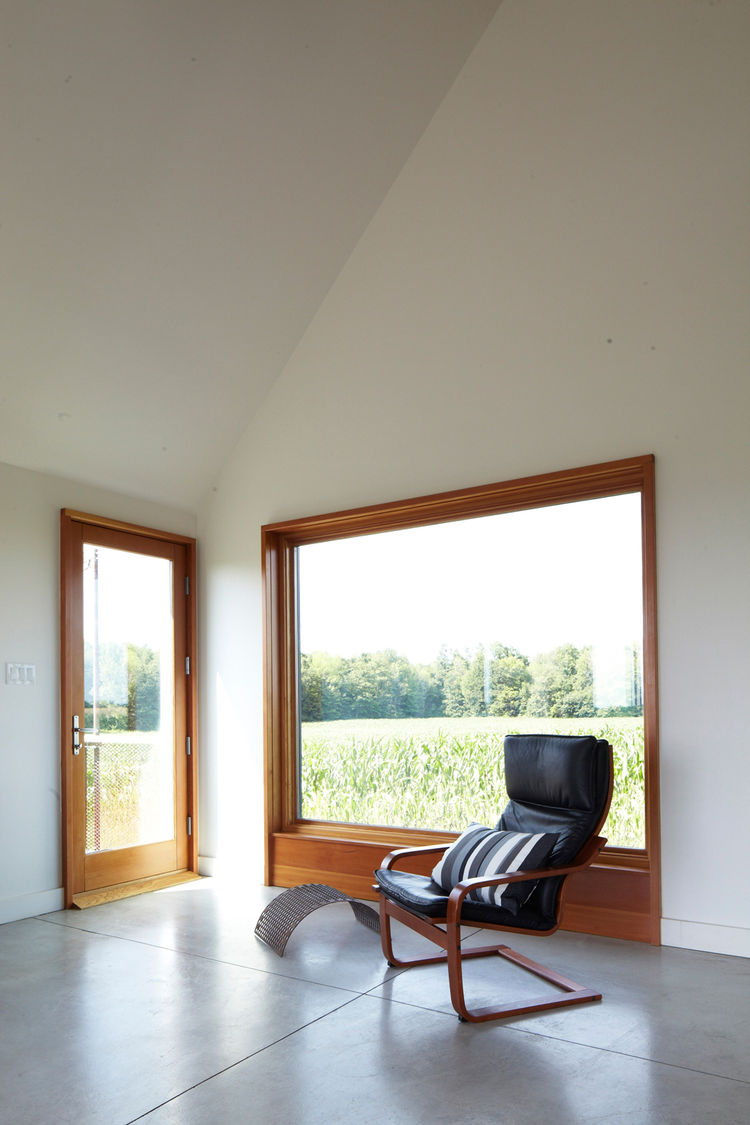Curved black leather chair by wood-framed corner windows