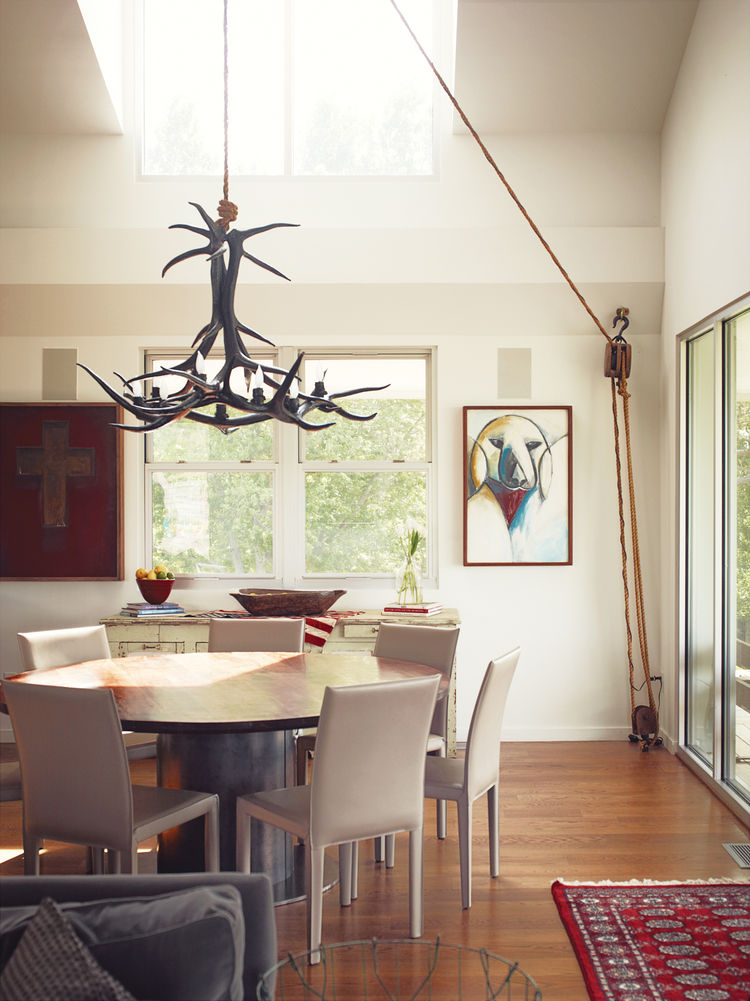 Modern dining room with antler chandelier and custom table