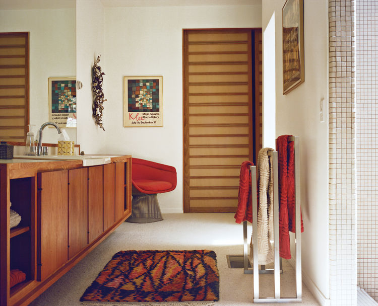 Modern bathroom with red Knoll chair and metal towel racks