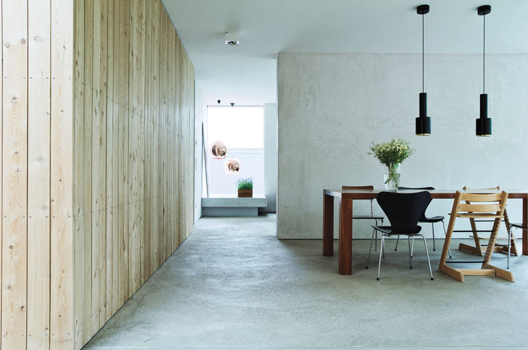 neutral colored dining room with concrete walls and floors