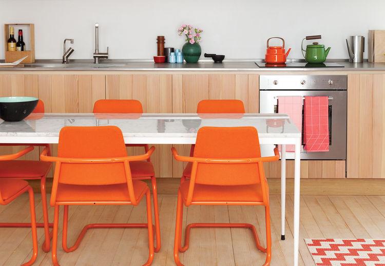 Modern custom-built kitchen with bright orange chairs