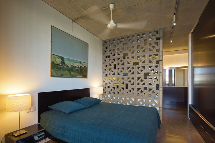 Modern bedroom with open-cell concrete block wall