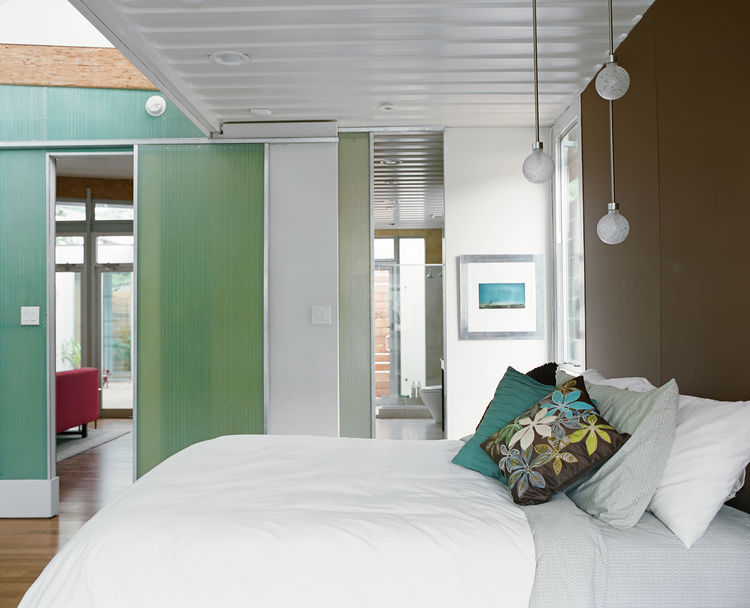 "The master bedroom is another place where Robertson placed emphasis on the existing size and shape of the containers. The room opens up to a clerestory window beyond the foot of the bed but the exposed edge of the container ceiling makes ""you almost feel"