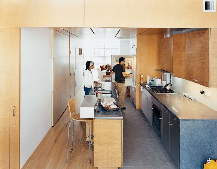 "In the kitchen, the architects contrasted the oak floor, bamboo cabinetry, and birch walls and ceiling with what architect Jonathan Knowles calls ""a family of grays"": granite floor tiles, limestone countertops, and the steel stairway. The birch wall behin"
