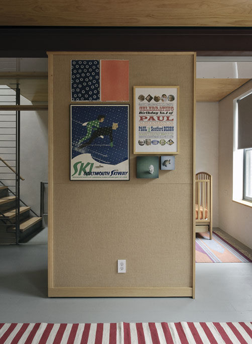 Hallway beam with vintage posters and striped rug