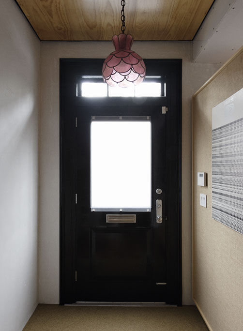 Front door entrance hallway with pink scalloped ceiling lamp