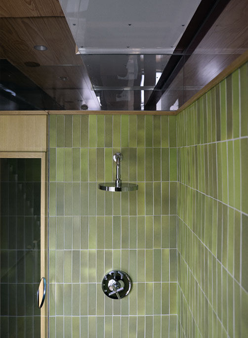 Bathroom shower lined with green Heath tiles and Kohler fixture