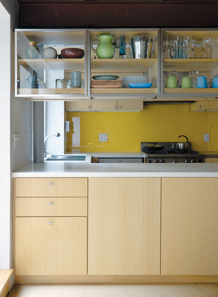 Modern kitchen with glass door cabinets and yellow back wall