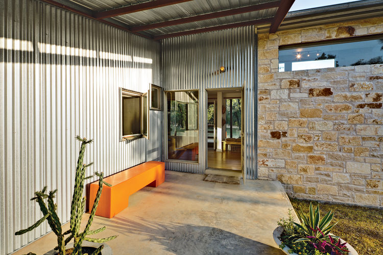 Front door entrance with orange bench and concrete flooring