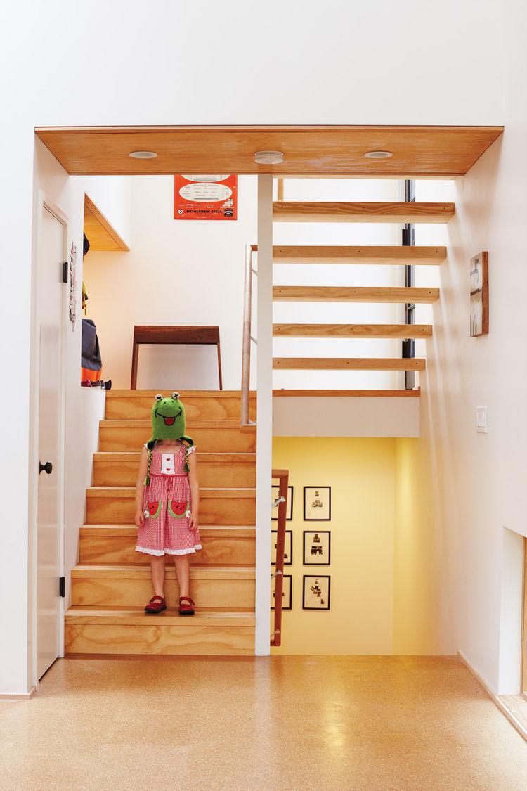 Little girl hanging out by the wood staircase