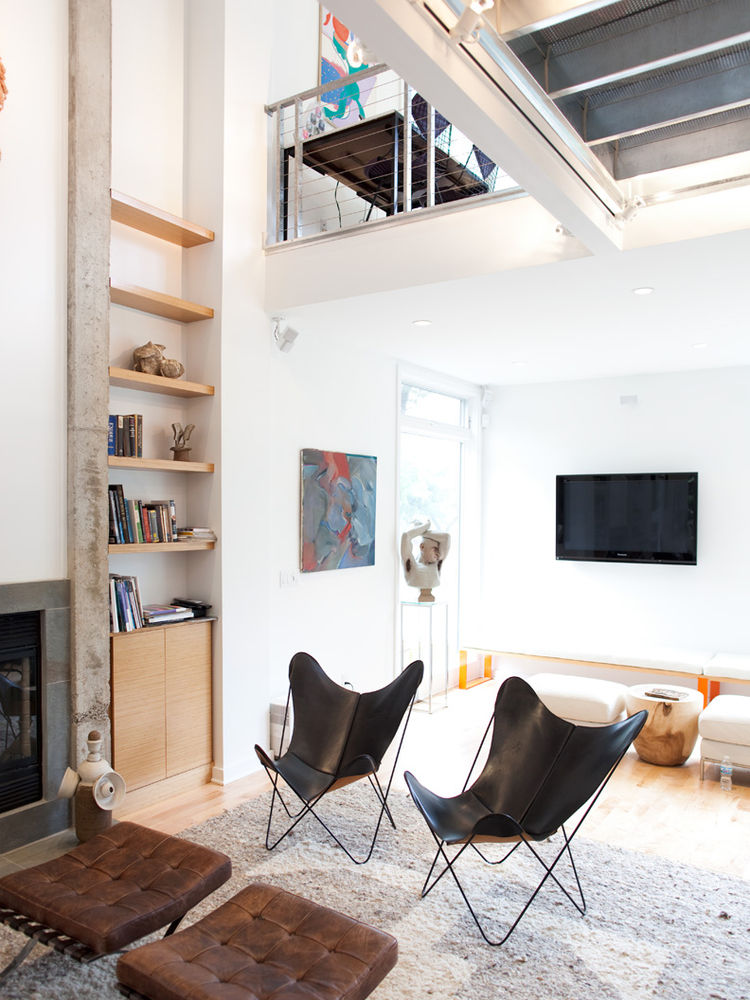 Living room with black leather butterfly chairs and a concrete-edged fireplace