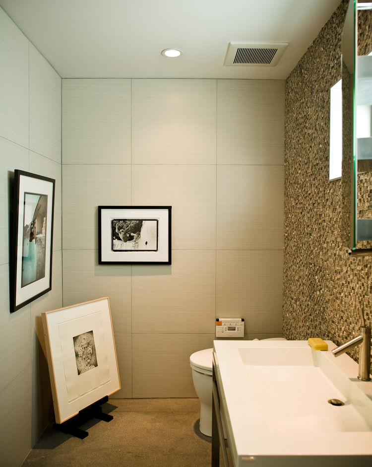 Simple office bathroom with framed original artwork