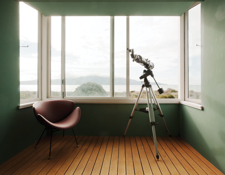 Salvaged chair and telescope by the window