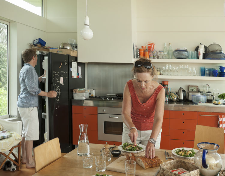 Couple prepping food in beach house kitchen