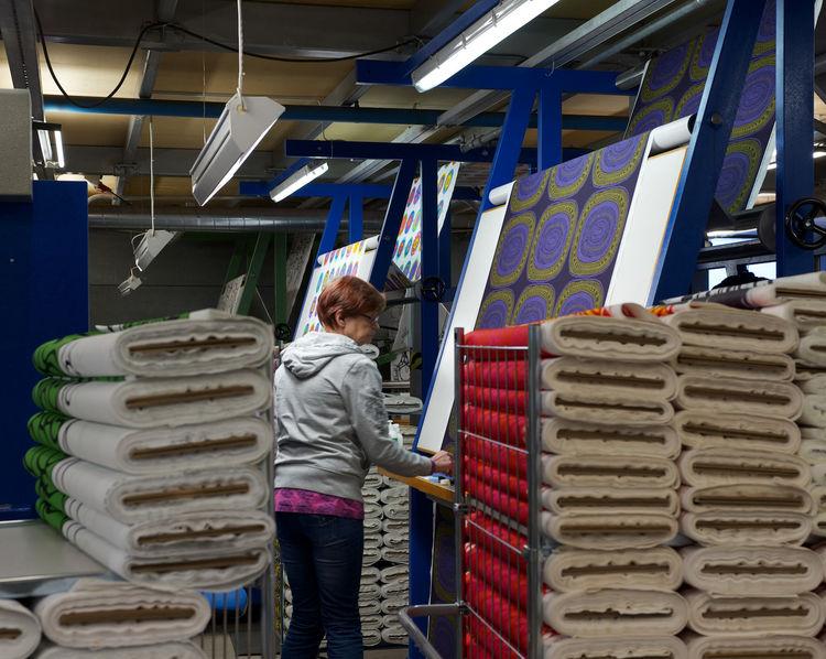 Marimekko employee inspecting a printed fabric