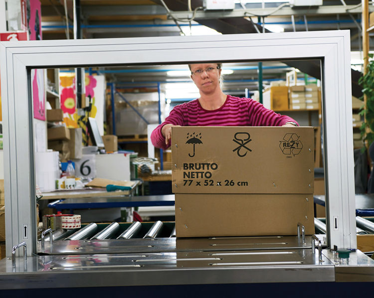 Marimekko employee packaging up printed fabrics